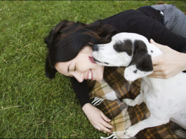 happy-girl-fun-loves-black-white-dog-on-grass-oudoors